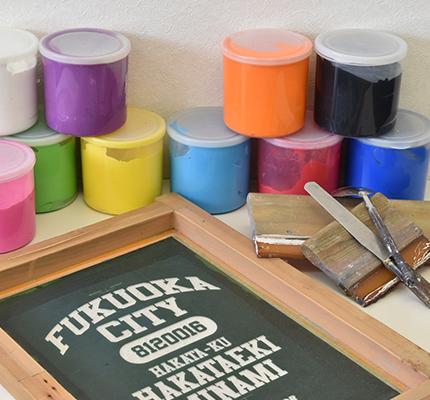 刺繍する機械の前で出来上がるのを待つスタッフの写真